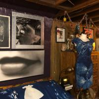 View of the artist's studio, filled with pictures, a dress on a mannequin, and other items and objects