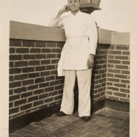 a man in kitchen uniform and apron on top of the roof