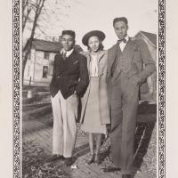 three people, 2 men with a woman between them photographed outside
