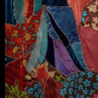 Blusa rosa de manga larga, con moño en la parte delantera y metida dentro de una falda larga de patchwork multicolor.