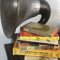 a stack of books next to a gramophone