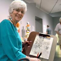 a woman holding up a drawing in the exhibition Jeffrey Gibson: Like a Hammer