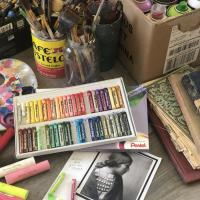 pastels, paint supplies, and black and white photo of an Indigenous woman on a table with other art supplies