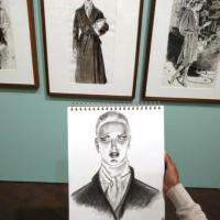a drop in drawing student holding a drawing in the Jim Howard exhibition