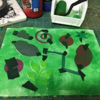 Green tempera paint is applied to the paper using a foam roller.