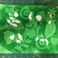 Overlapping green and white shapes are created on the paper.