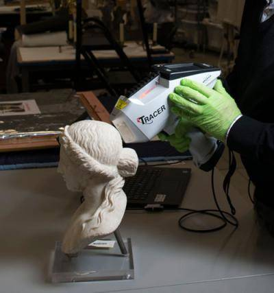 Staffer using tool to clean head of Apollo statue