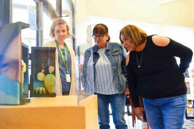 Teachers and staff at the Denver Art Museum looking at Outside In: Contemporary Landscape Art exhibition setup in community center
