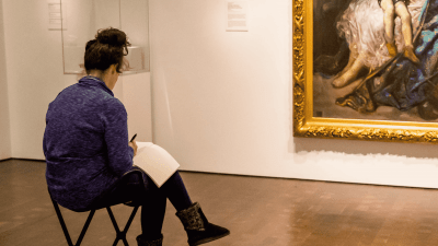 Person sitting in a gallery at the Denver Art Museum writing in a journal