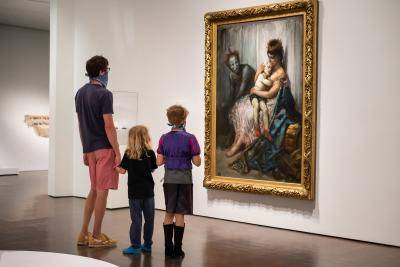 Father looking at a painting with his son and daughter