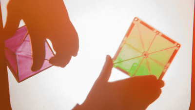 A child's hand playing with shapes, light, and colors