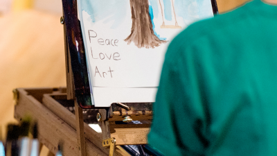 "Child painting with ""Peace Love Art"" written in bottom left-hand corner"