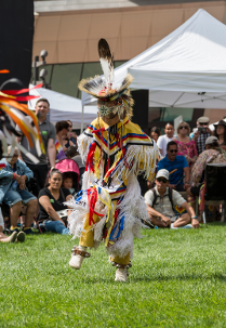 Dancing child dressed in traditional Native American attire at Denver Art Museum's Powwow