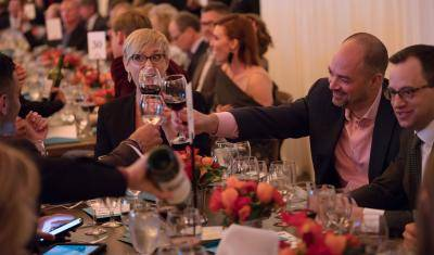 Guests clinking their wine glasses at an Uncorked event