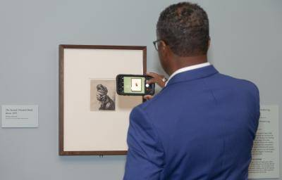 Gentleman taking a photo of an artwork with his cell phone
