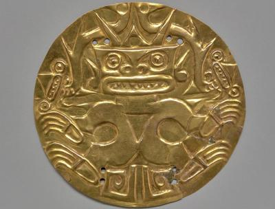 gold round breast plate engraved with a figure on it