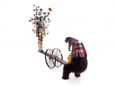a seesaw with a mannequin with vintage toys on it on one side and a hairy figure on the other side