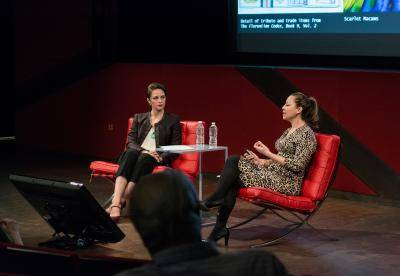 Two women in conversation on stage at a museum lecture