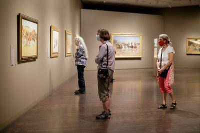 Three masked women looking at an artwork while social distancing