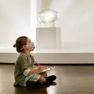 a girl sits on the floor and draws in a gallery