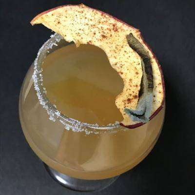 a glass filled with a cocktail with an apple slice on top