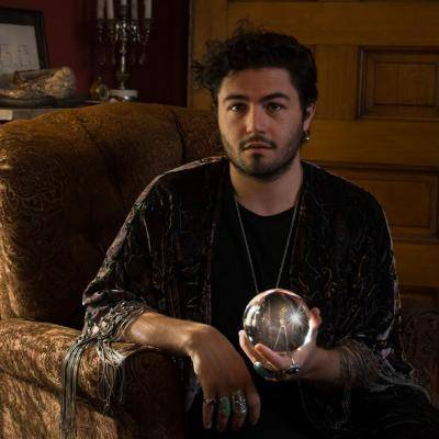 Cooper Kaminsky in a chair holding a mirror ball in his left hand