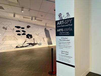 Instruction sign and mural for the Art Spy: Giant Seek and Find game in the galleries