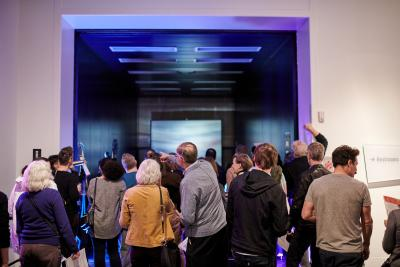 Visitors gather in the museum to look at a digital projection