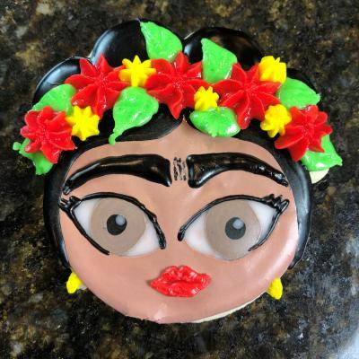 a cookie that looks like Frida Kahlo's head with red and yellow flowers in a flower crown