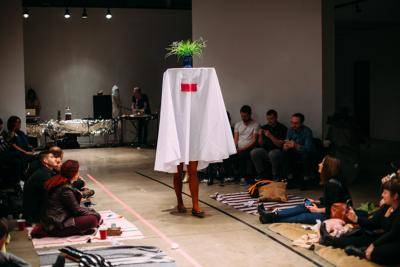 Woman walking own a runway dressed as a table with a plant on top of it
