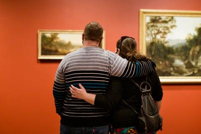 Couple embracing while gazing at paintings