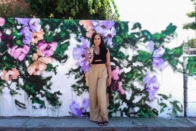 Ashley Joon standing in front of one of her outdoor murals of flowers