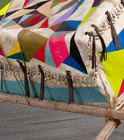 Detail of oversized rawhide box with painted geometric shapes in bright colors, on repurposed tipi poles