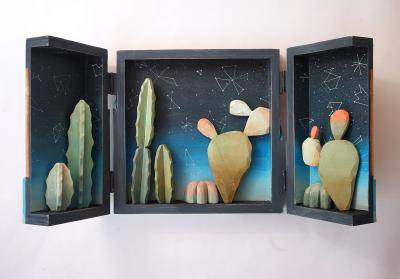 A diorama triptych featuring cut outs of cacti and the night sky