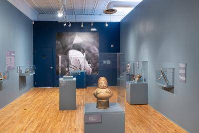 Gallery view of the Rhythm and Ritual exhibition with ancient musical instruments inside glass cases and a picture of a musician on the wall