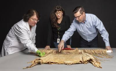 DAM curator John Lukavic examining an upper Missouri shirt.
