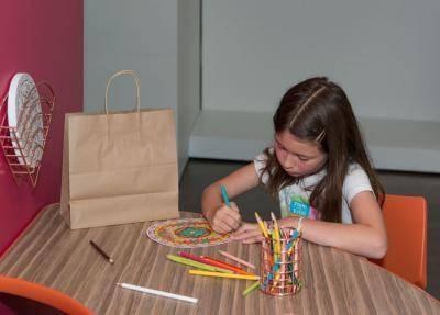 girl coloring a mandala coloring page