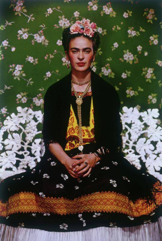 Frida Kahlo sitting with arms folded in lap against a backdrop of green and white