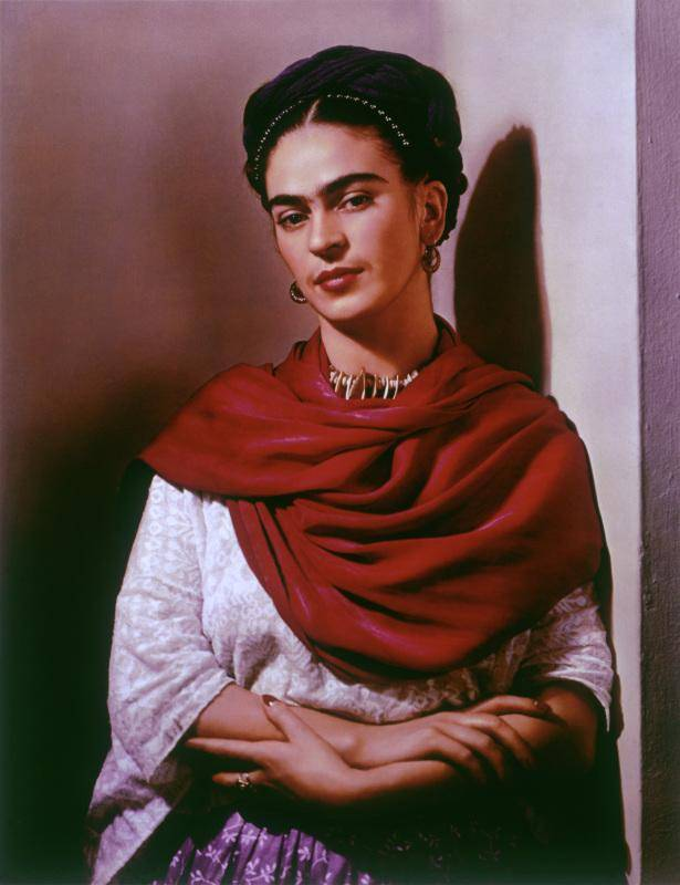 Frida Kahlo leaning against a wall for a portrait, wearing a red scarf
