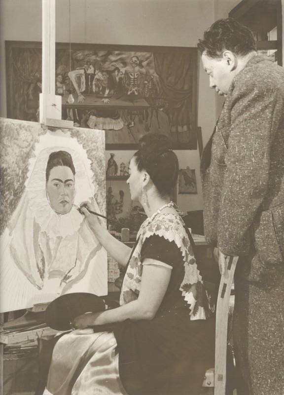 Black-and-white photograph of Frida Kahlo painting while Diego Rivera watches over her shoulder