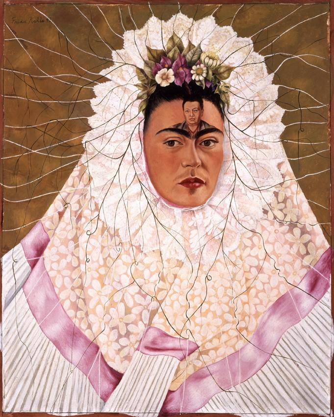 Frida Kahlo covered in a white and light pink dress, so much so that only her head is peaking through