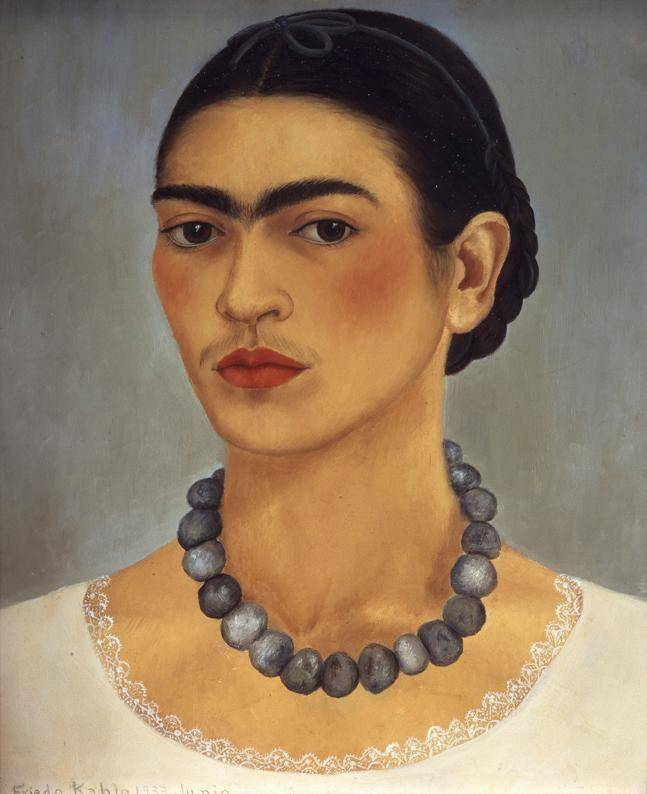 Frida Kahlo from the neck up, wearing a prominent gray beaded necklace