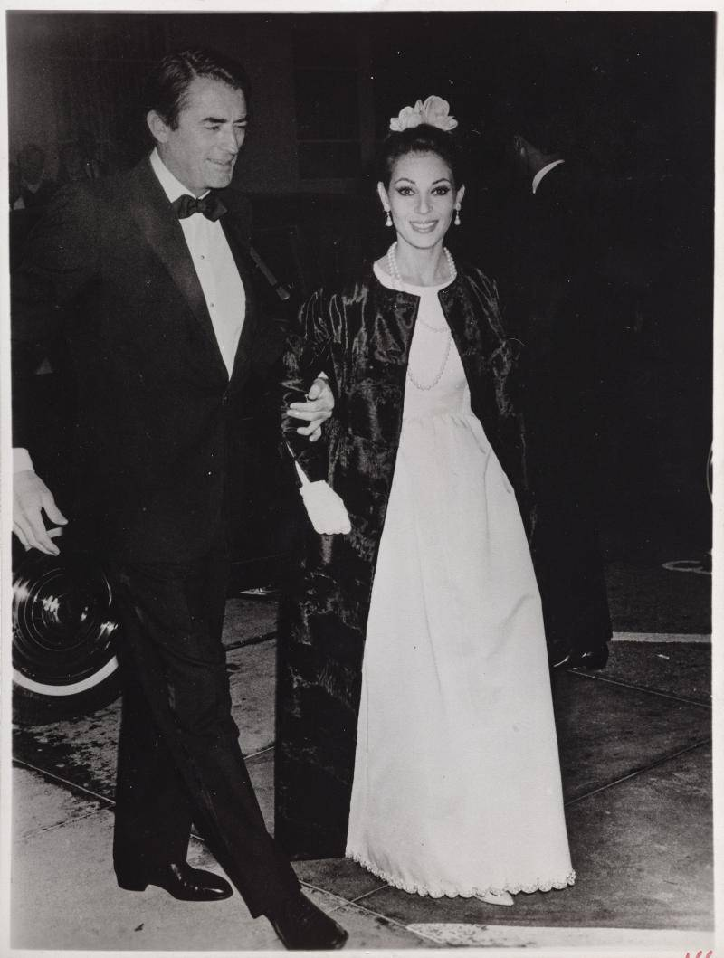 Veronique in a white dress and Gregory in a tuxedo arriving at a film premiere