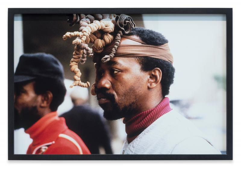 A Black man wearing an elaborate head piece.