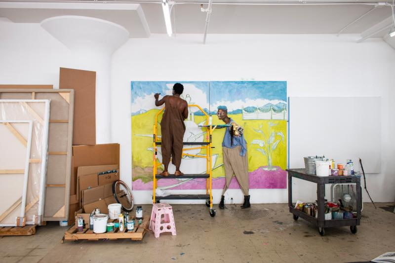 Wide shot of the artist working in his studio while on a ladder