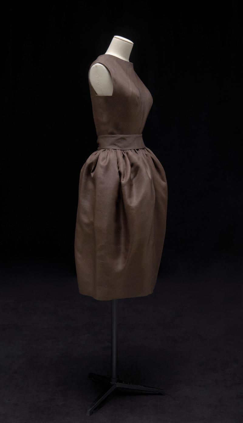 Side view of a brown couture dress with a belt