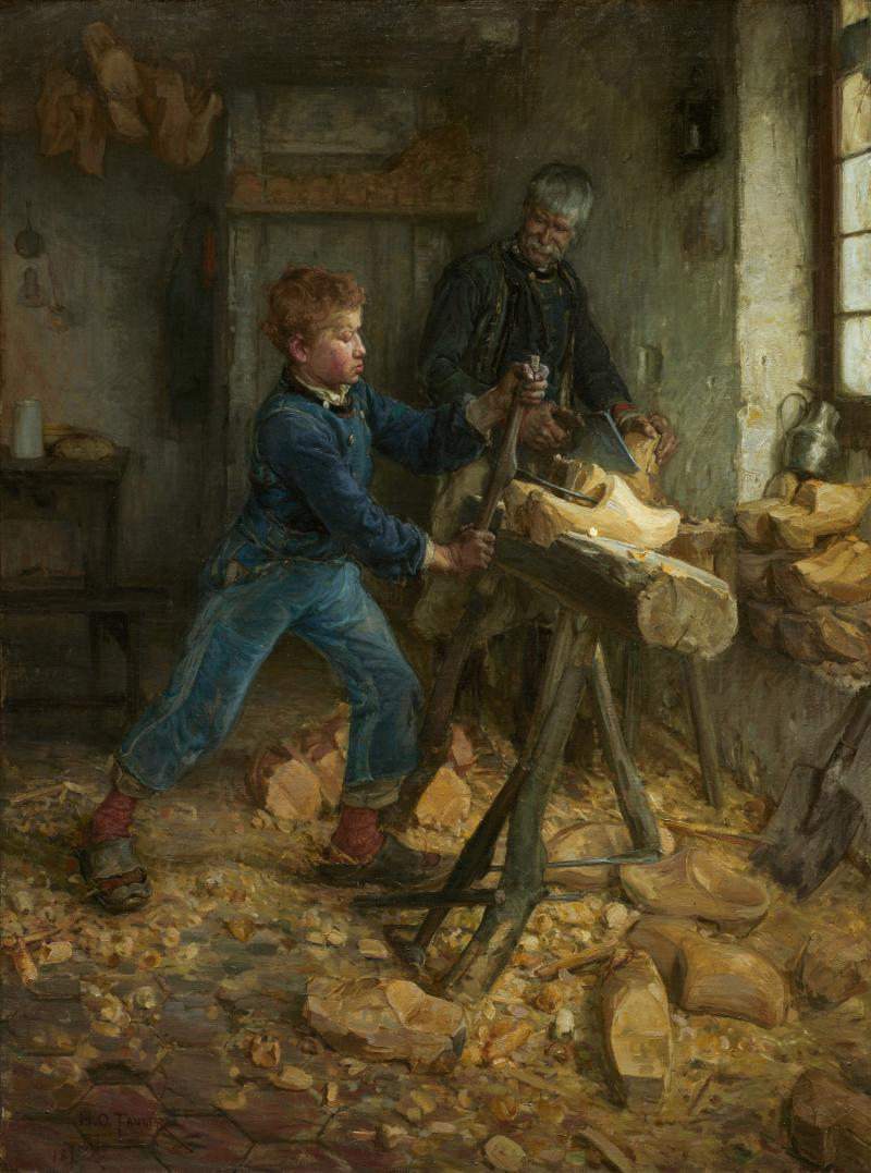 A young boy carving wood as his father supervises.