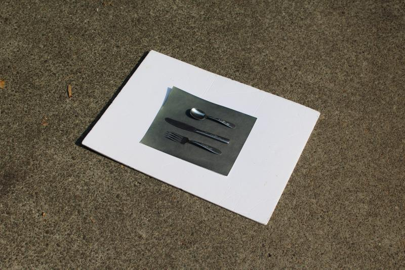 A piece of paper with silver kitchen cutlery at the center