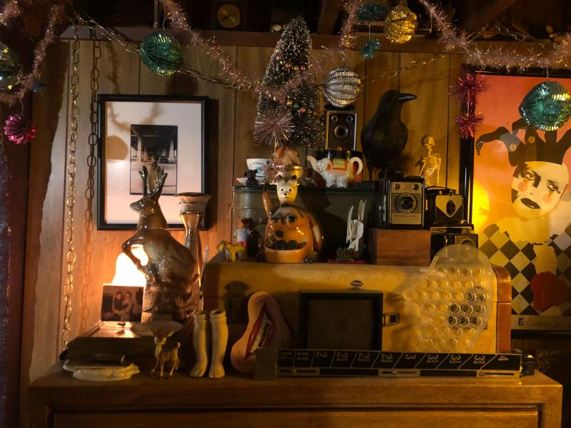 View of a wall and shelf with pictures, knick knacks, statues, lights, garland, and other decorations on it
