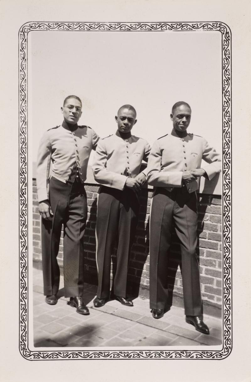 three men in bellhop uniforms on the roof